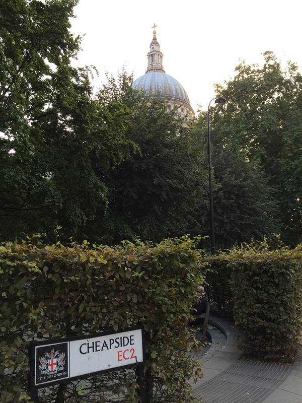 St paul's cathedral above the green bushes with a sign called Cheapside
